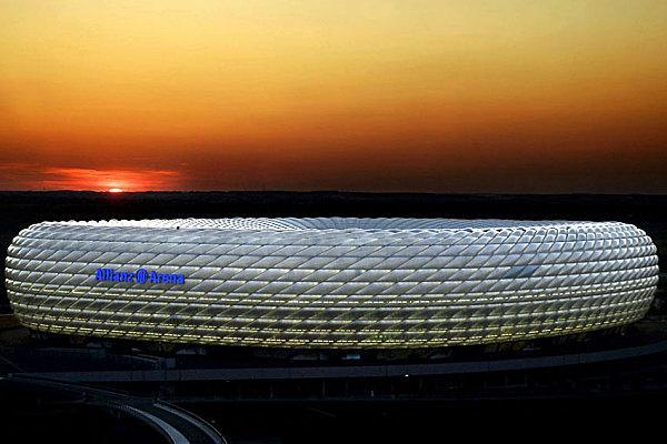 «Альянц-Арена» Где находится: Мюнхен, Германия Год постройки: 2005 Чем необычен: оформлением фасада. Именно благодаря ему архитектурное бюро «Херцог & де Мерон» и выиграло конкурс на проектирование нового стадиона в Мюнхене. «Альянц-Арена» покрыта 2874 ромбовидными «подушками» из пластика, в которые вмонтированы люминесцентные трубки. Полимер, использованный для изготовления «подушек», более чем в 100 раз легче стекла и при этом пропускает не менее 95% солнечных лучей. Во время игр национальной сборной стадион излучает белый свет, а когда выступают местные клубы, светится их родными цветами: красным для «Баварии» и голубым для «Мюнхен 1860»